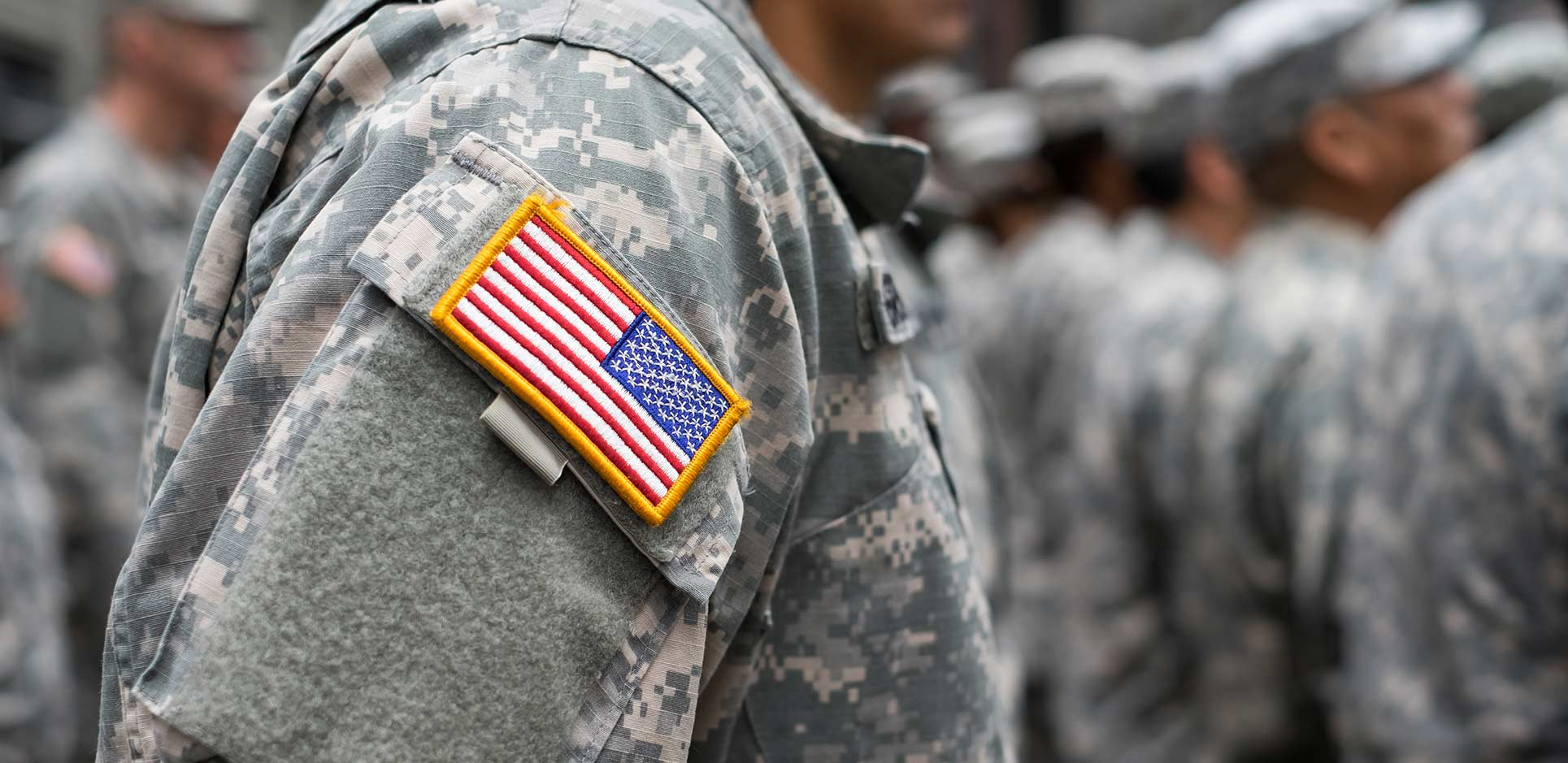 Flag patch on a military sleeve, blurred formation in background