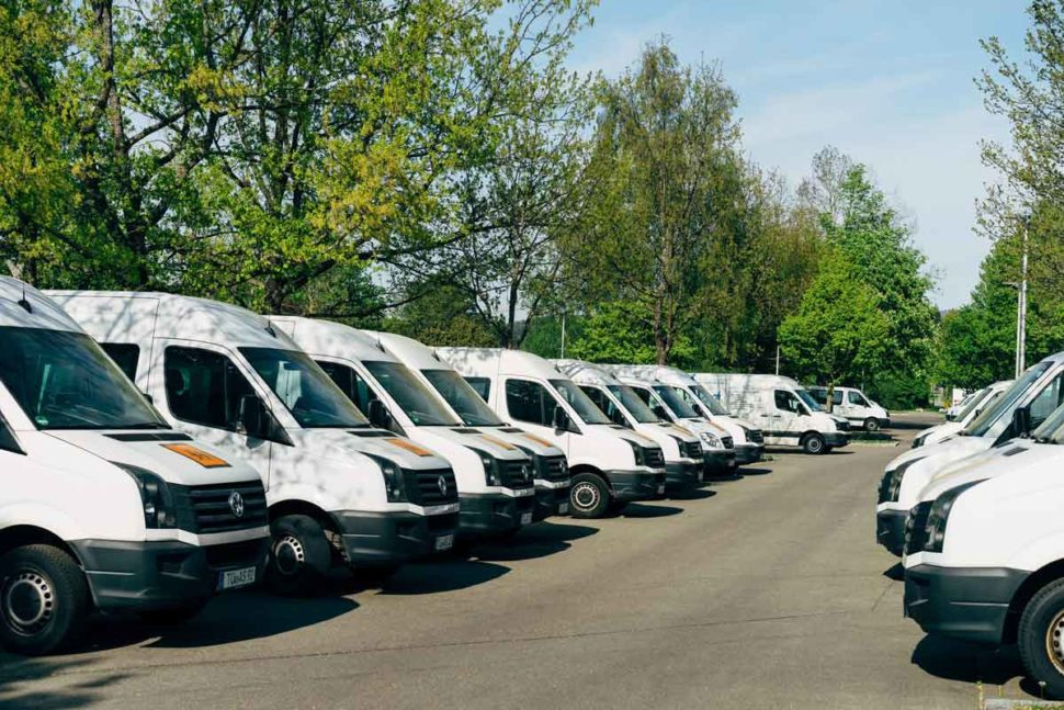two rows of white fleet vans parked in a lot