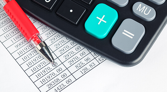 On a spreadsheet listing dollar amounts, a calculator and red pen sit ready for use.