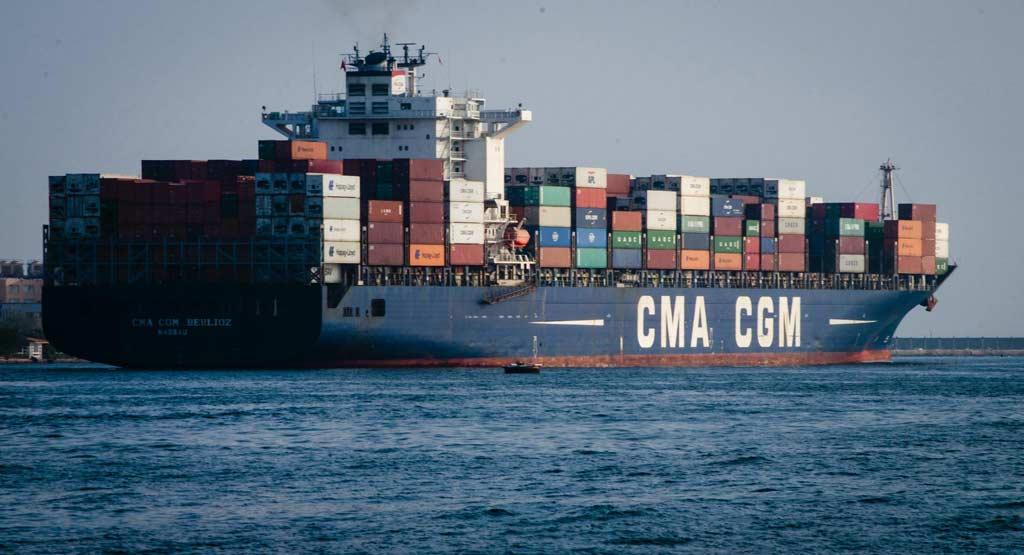 A cargo ship carrying countless containers on sea during daytime