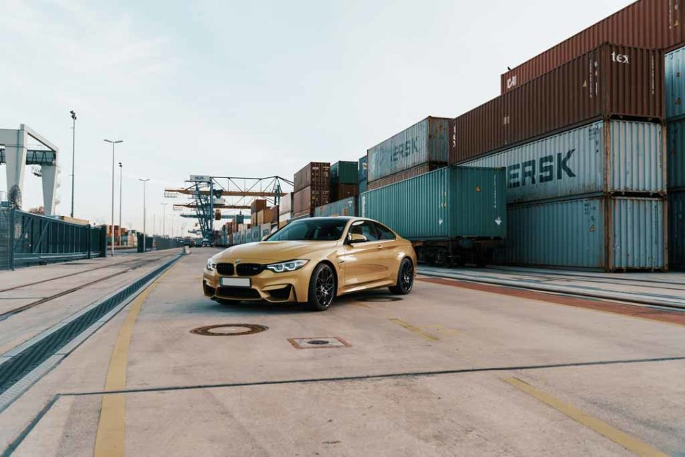 A gold-colored BMW in a seaport parked in front of shipping containers